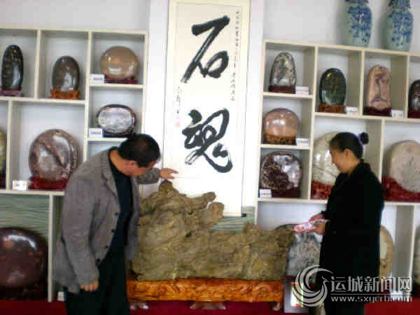 刘金京在向外来顾客介绍心仪的奇石文化产品