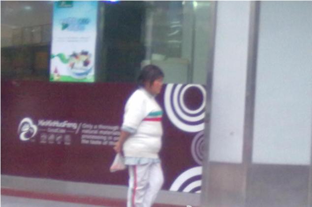 一乞丐穿着鹤华中学的校服在街上扮模特走天桥